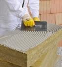 Die Dämmplatten des WDVS werden mit Klebemörtel bestrichen. Foto: Saint-Gobain Weber