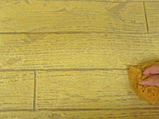 Überschüssige Lasur mit einem Schwamm abnehmen. Foto: Baumit
