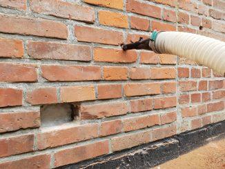 Die Düse des Einblasschlauchs wird in die Löcher in der Fugenebene gesetzt. Foto: Ecofibre Dämmstoffe GmbH