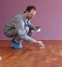 Das Wachs mit dem Spachtel auf den Holzboden auftragen. Foto: Auro