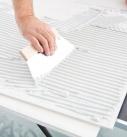 Der Fugenspachtel wird vollflächig auf der Plattenrückseite aufgezogen. Foto: Saint-Gobain Rigips GmbH